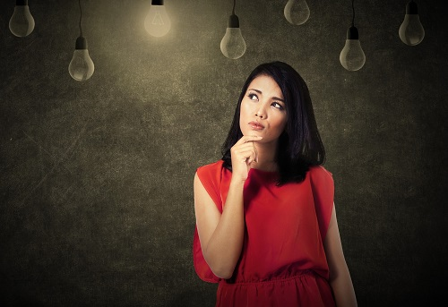 Asian woman thinking while looking at bright lightbulbs
